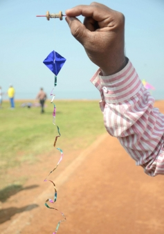 A participant displaying a small kite at the 26th edition of International Kite festival