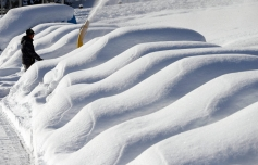 A worker clears a parking place from snow in Zuoz, Switzerland